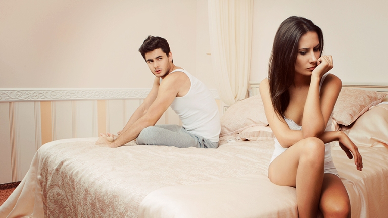 unhappy-young-couple-sitting-on-bed