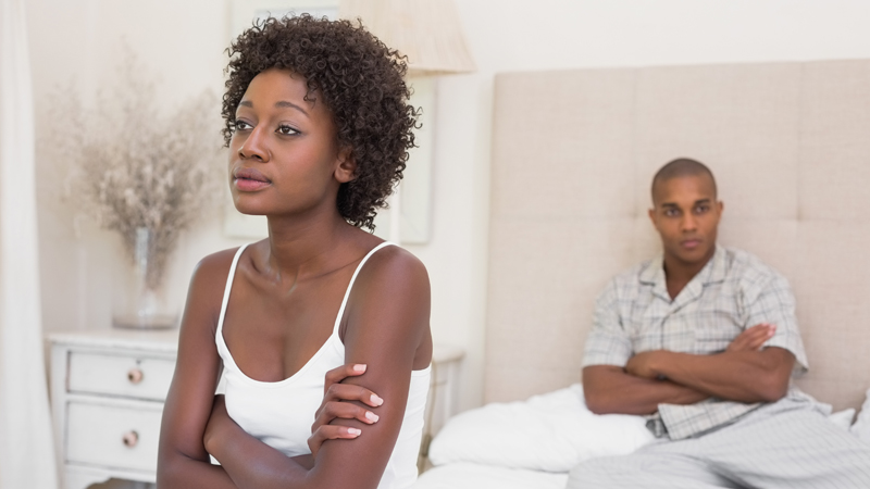 Unhappy couple not speaking to each other on bed at home in the
