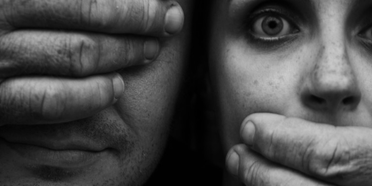 Hands Covering Man's Eye and Startled Woman's Mouth